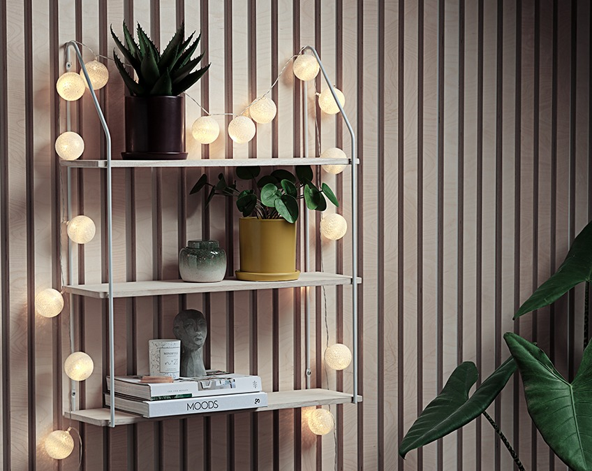 Light string draped around a wall shelf