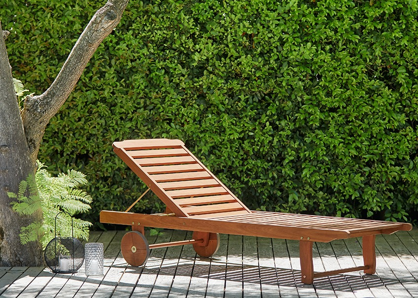 Wooden sun lounger on a sunny patio