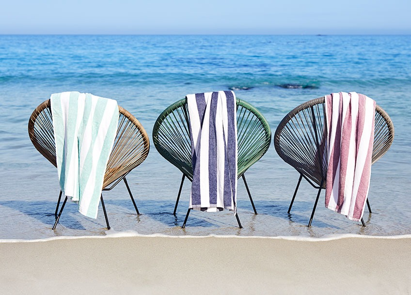 Garden lounge chairs on a beach with large beach towels hanging from the back