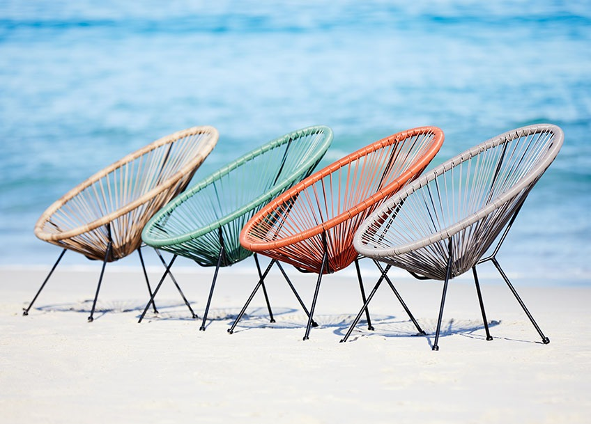 Four garden lounge chairs in different colours on a beach
