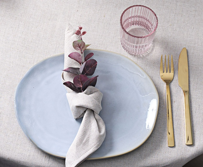 Decorative table setting with plate, cloth napkin, glass and knife and fork