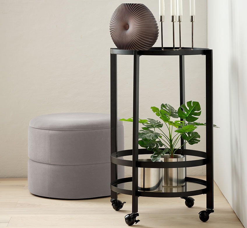Grey pouffe with storage and a trolley with a vase, candlesticks and a plant pot