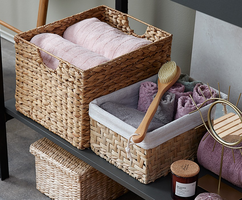 Nicely folded towels in wicker storage baskets on a shelf