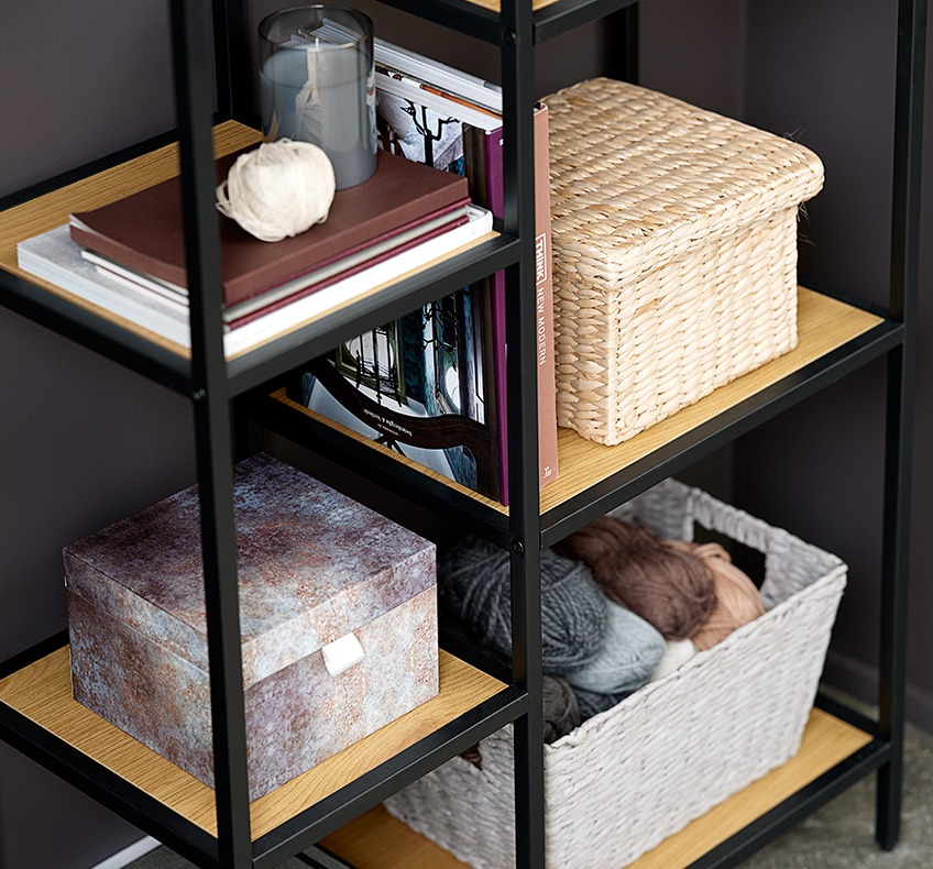 Asymmetrical bookcase with wicker storage boxes