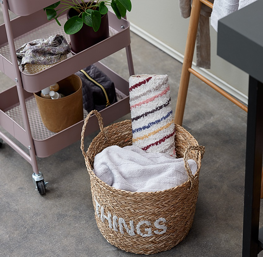 Bathroom accessories on a trolley next to a wicker storage basket with towels and a bath mat in it