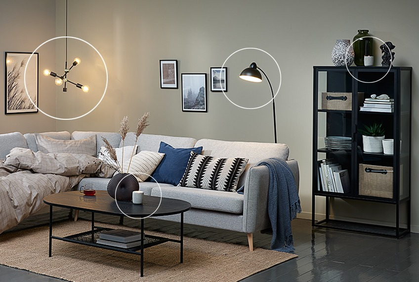 Duvet placed in corner sofa, pendant with light bulbs, modern floor lamp and display cabinet