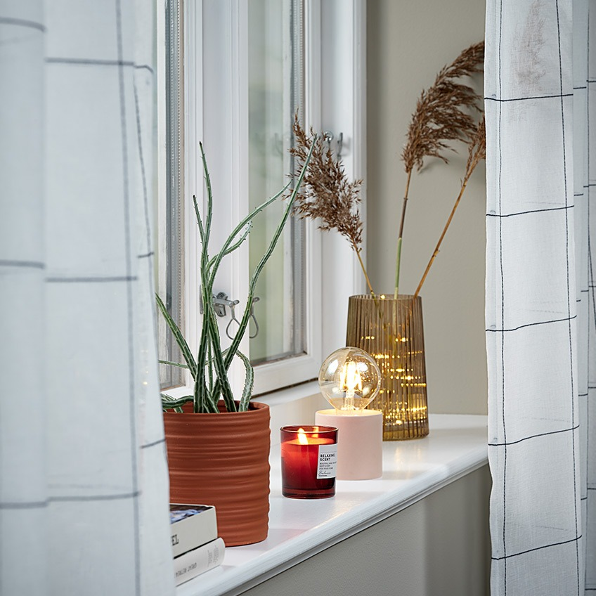 Lightweight curtains in a window with plant pot, scented candle, battery lamp and vase in the windowsill