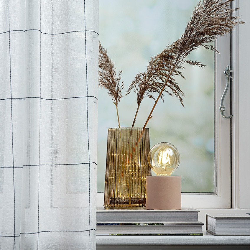 Lightweight curtains in a window with a vase and a battery lamp in the windowsill