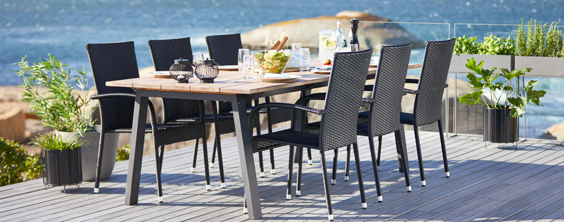 S378812 PADHOLM table and GUDHJEM chairs on a patio by the sea