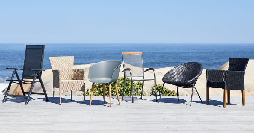 Dining chairs on patio by the beach